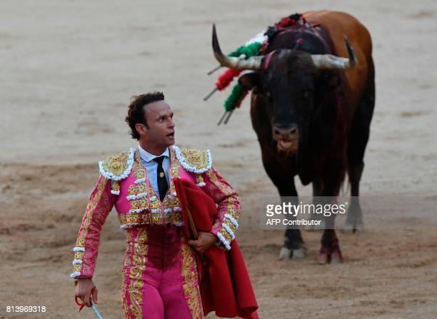 Spanish matador Antonio Ferrera walk with a Nunez del Cuvillo's fighting bull in background during the seventh bullfight of the San Fermin Festival...