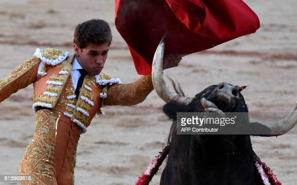 Spanish matador Gines Marin performs a pass to a Nunez del Cuvillo's fighting bull during the seventh bullfight of the San Fermin Festival in...
