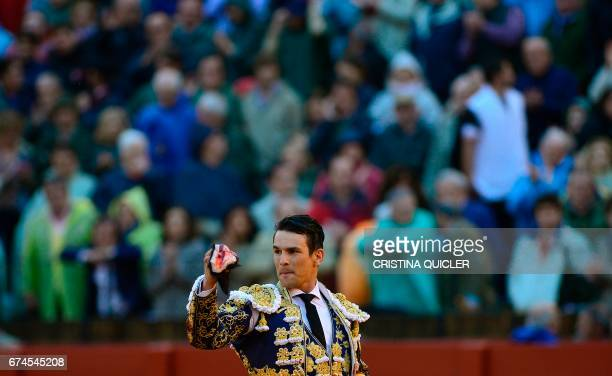 Spanish matador Jose Maria Manzanares holds the bull's ear as he acknowledges the public during a bullfight at the Maestranza bullring in Sevilla on...
