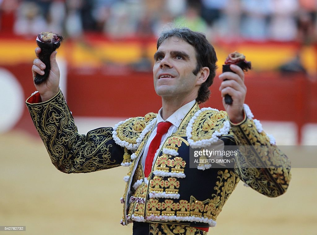 Spanish matador Jose Tomas acknowledges the crowd as he holds two bull' ears during the San Juan Feria at Alicante bullring on June 24, 2016. / AFP / ALBERTO