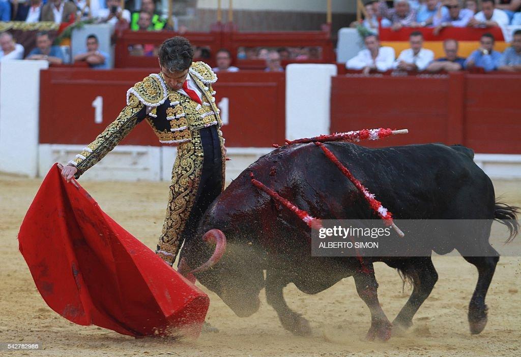 Spanish matador Jose Tomas performs a pass to a bull during the San Juan Feria at Alicante bullring on June 24, 2016. / AFP / ALBERTO