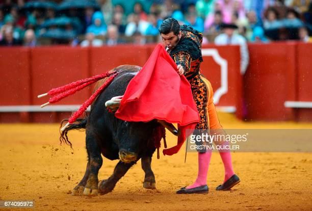Spanish matador Morante de La Puebla performs a pass with muleta on a bull during a bullfight at the Maestranza bullring in Sevilla on April 27 2017...