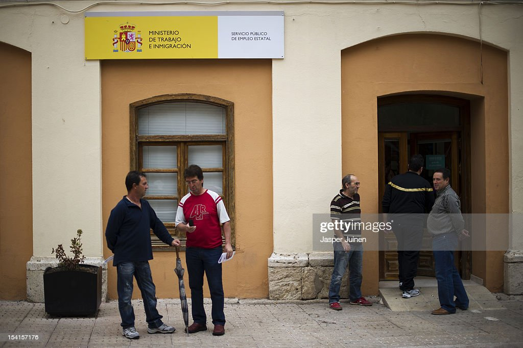 Spanish men stand in front of an unemployement office on October 11, 2012 in the small industrial town of Villacanas, Spain. During the boom years, where in its peak Spain built some 800,000 houses a year, more than Britain, Germany and France combined, and millions of wooden doors where needed, the people of Villacanas were part of a proud elite enjoying high wages and permanent jobs. Almost all of those doors used came from this small industrial town in the La Mancha province, some seven million a year, leaving with truck loads at the same time, from the now empty and silent Villacanas industrial park. With Spain in recession and the housing bubble busted, the door industry is shattered and unemployment in Villacanas, zero for nearly a generation, is rising fast.