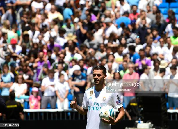 Spanish midfielder Dani Ceballos gives the thumbs up as he poses on the pitch during his presentation as new football player of the Real Madrid CF at...