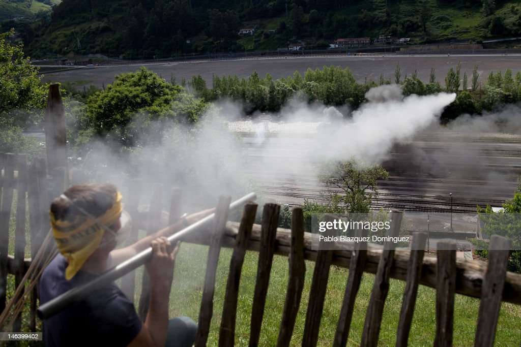 A Spanish miner launches a firecracker during clashes with riot police in the motorway A66 near Mieres on June 15, 2012 in northern Spain. Spanish coal miners are staging a nationwide strike organised by unions opposed to subsidy reductions from 300 million to 110 million Euros.