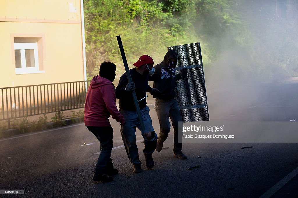 Spanish miners run away from tear gas launched by riot police at the Soton mine June 15, 2012 in El Entrego, near Oviedo in northern Spain. Spanish coal miners are staging a nationwide strike organised by unions opposed to subsidy reductions from 300 million to 110 million Euros.