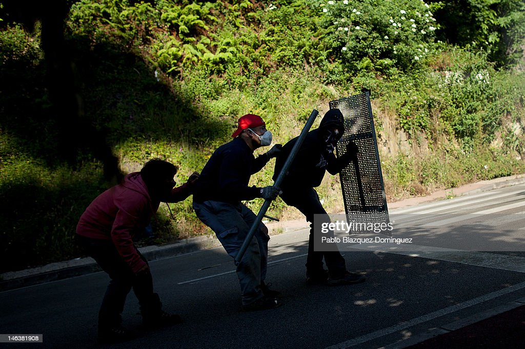 Spanish miners walk away form riot police behind a home made shield at the Soton mine June 15, 2012 in El Entrego, near Oviedo in northern Spain. Spanish coal miners are staging a nationwide strike organised by unions opposed to subsidy reductions from 300 million to 110 million Euros.