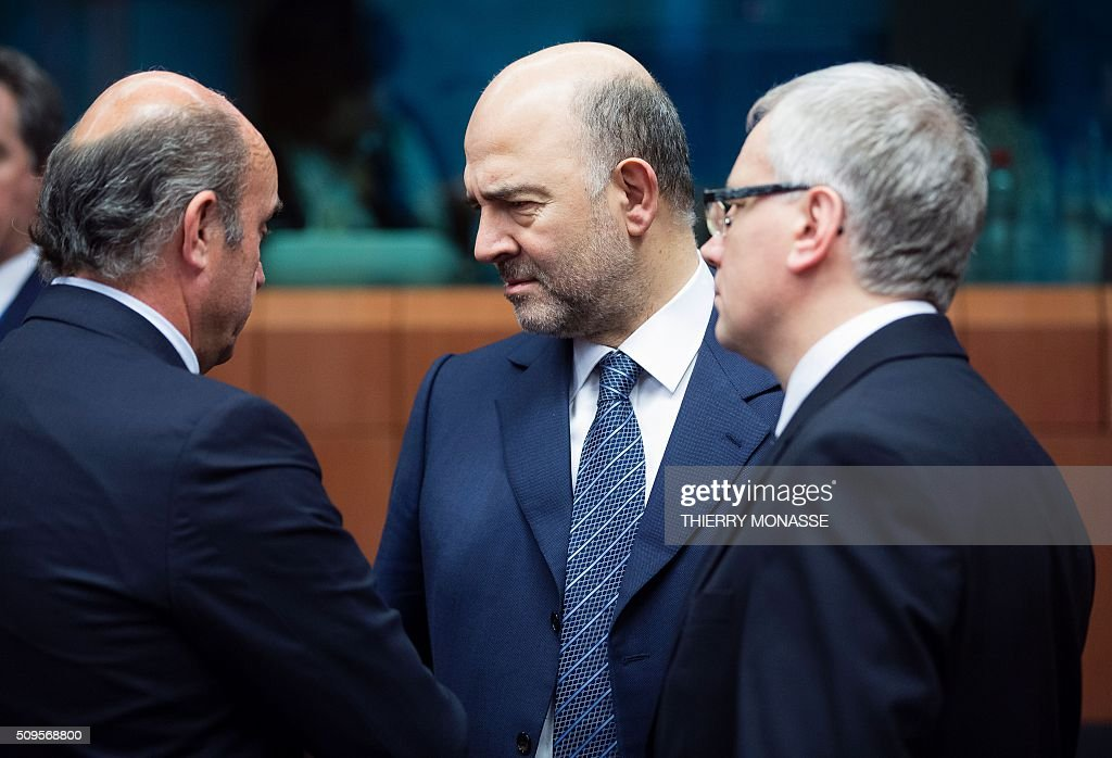 Spanish Minister of Economy and Competitiveness Luis De Guindos Jurado (L) talks with EU Economic and Financial Affairs, Taxation and Customs Commissioner Pierre Moscovici (C) and the Lithuanian Finance Minister Rimantas Sadzius (R) prior to a meeting of Eurogroup ministers at the European Council headquarters in Brussels on February 11, 2016. / AFP / THIERRY MONASSE