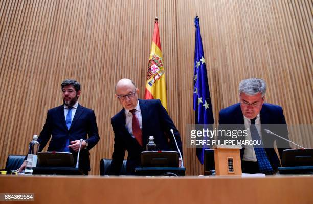 Spanish Minister of Finance and Public Services Cristobal Montoro arrives to a press conference flanked by State secretaries Albert Nadal and Jose...