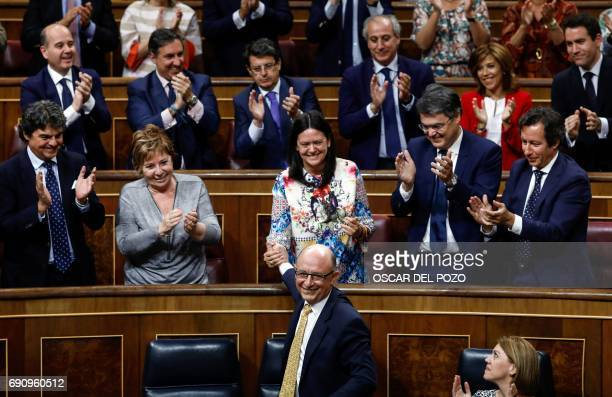Spanish Minister of the Treasury and Public Function Cristobal Montoro is congratulated by the Popular group's MPs at the end of the parliamentary...