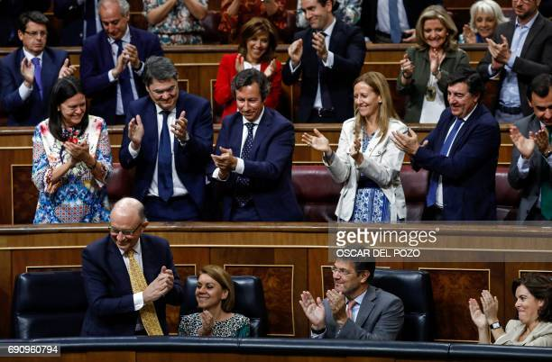Spanish Minister of the Treasury and Public Function Cristobal Montoro applauds beside the Popular group's MPs at the end of the parliamentary...