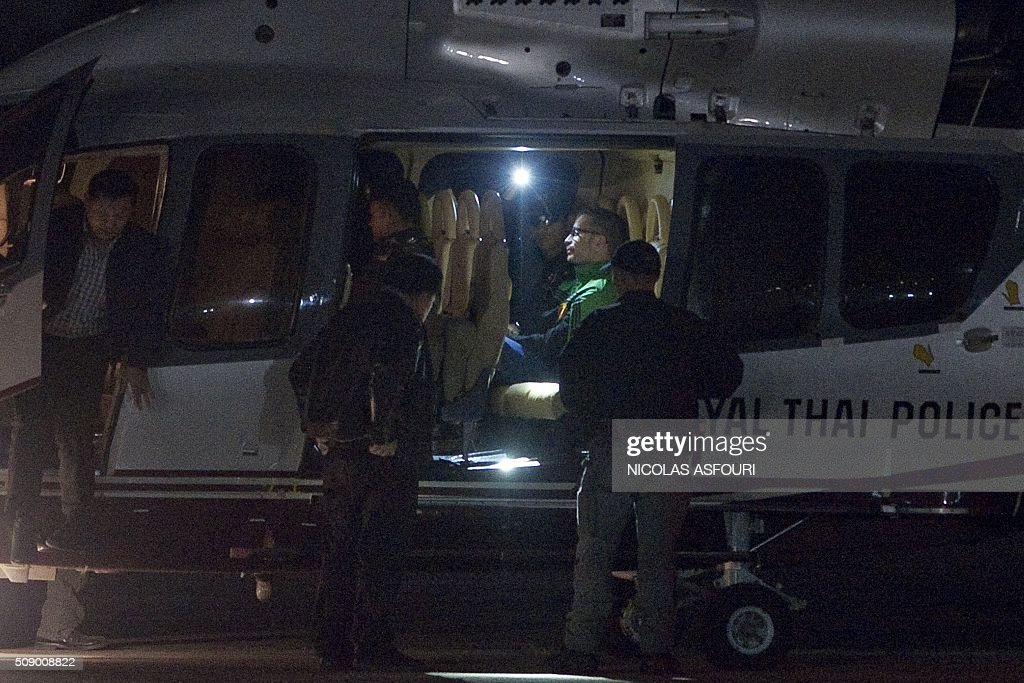 Spanish national Artur Segarra (C, in green), 36, arrives by helicopter at the Tha Raeng police aviation base in Bangkok on February 8, 2016. The prime suspect in the grisly murder and dismemberment of a Spanish national in Bangkok was returned to Thailand after his arrest in Cambodia, police said. AFP PHOTO / Nicolas ASFOURI / AFP / NICOLAS ASFOURI