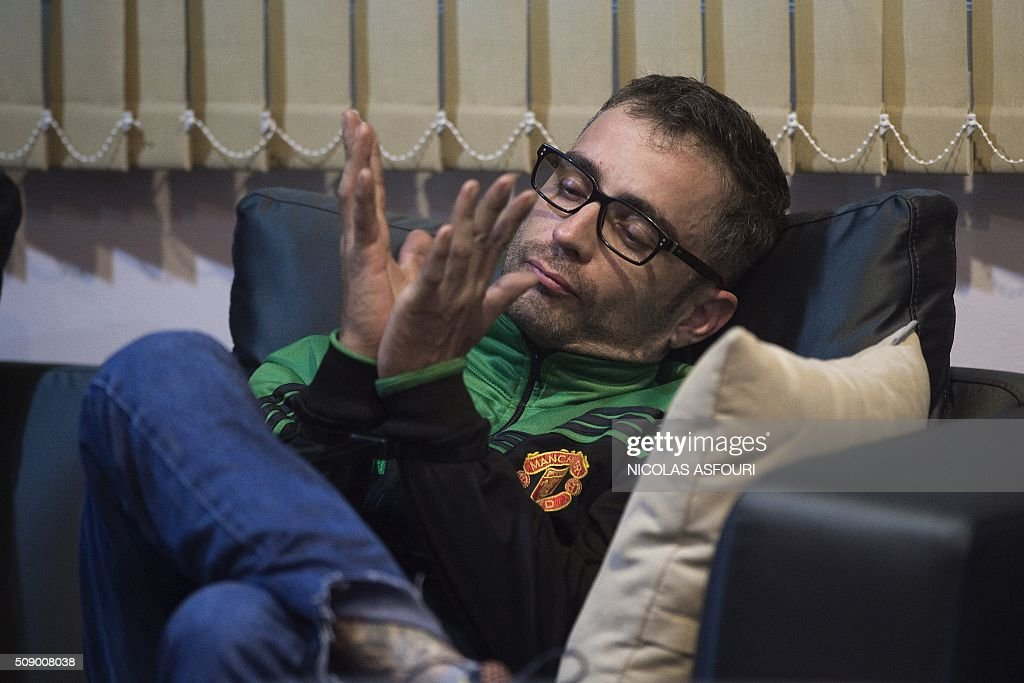 Spanish national Artur Segarra, 36, looks at his handcuffed hands on a couch while guarded by a police officer (unseen) after he arrived by helicopter at the Tha Raeng police aviation base in Bangkok on February 8, 2016. The prime suspect in the grisly murder and dismemberment of a Spanish national in Bangkok was returned to Thailand after his arrest in Cambodia, police said. AFP PHOTO / Nicolas ASFOURI / AFP / NICOLAS ASFOURI