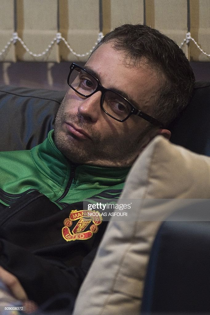 Spanish national Artur Segarra, 36, looks on from a couch while guarded by a police officer (not seen) after he arrived by helicopter at the Tha Raeng police aviation base in Bangkok on February 8, 2016. The prime suspect in the grisly murder and dismemberment of a Spanish national in Bangkok was returned to Thailand after his arrest in Cambodia, police said. AFP PHOTO / Nicolas ASFOURI / AFP / NICOLAS ASFOURI