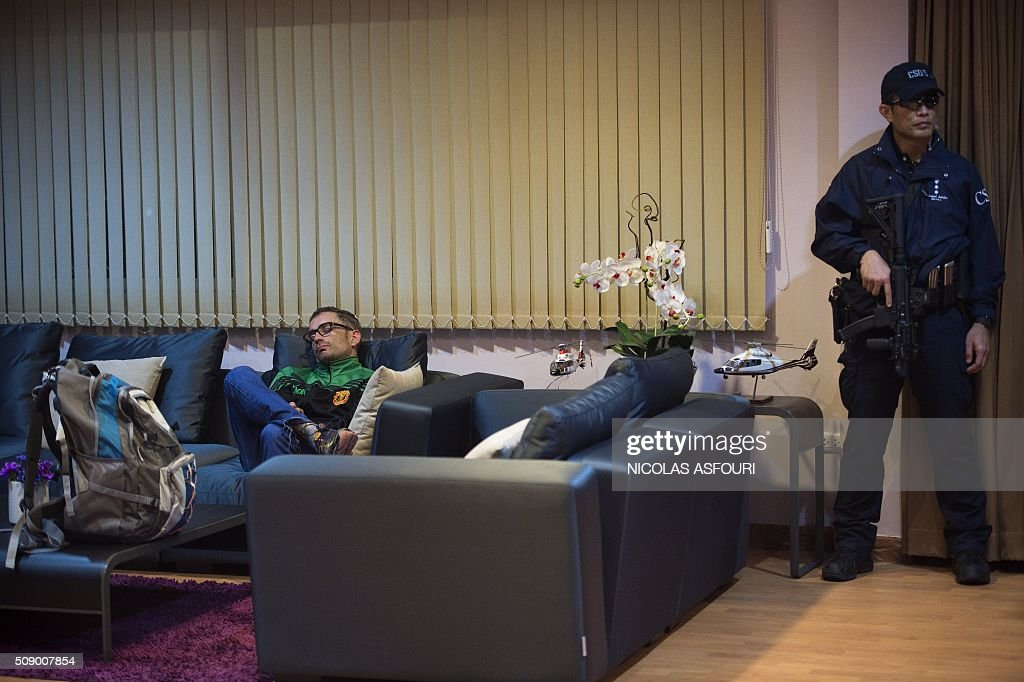 Spanish national Artur Segarra (L), 36, rests on a couch while guarded by a police officer (R) after he arrived by helicopter at the Tha Raeng police aviation base in Bangkok on February 8, 2016. The prime suspect in the grisly murder and dismemberment of a Spanish national in Bangkok was returned to Thailand after his arrest in Cambodia, police said. AFP PHOTO / Nicolas ASFOURI / AFP / NICOLAS ASFOURI