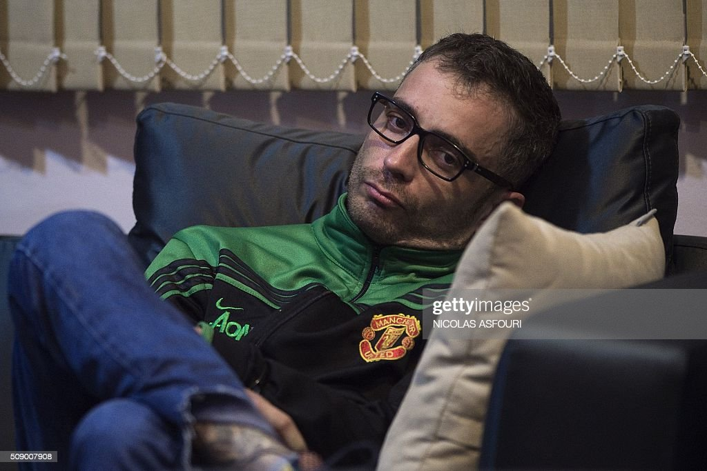 Spanish national Artur Segarra, 36, rests on a couch while guarded by a police officer (unseen) after he arrived by helicopter at the Tha Raeng police aviation base in Bangkok on February 8, 2016. The prime suspect in the grisly murder and dismemberment of a Spanish national in Bangkok was returned to Thailand after his arrest in Cambodia, police said. AFP PHOTO / Nicolas ASFOURI / AFP / NICOLAS ASFOURI