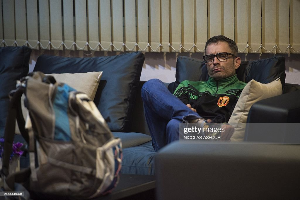 Spanish national Artur Segarra, 36, sits on a couch while guarded by a police officer (unseen) after he arrived by helicopter at the Tha Raeng police aviation base in Bangkok on February 8, 2016. The prime suspect in the grisly murder and dismemberment of a Spanish national in Bangkok was returned to Thailand after his arrest in Cambodia, police said. AFP PHOTO / Nicolas ASFOURI / AFP / NICOLAS ASFOURI