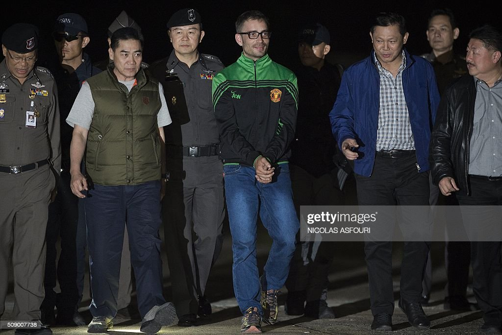 Spanish national Artur Segarra (C), 36, walks handcuffed surrounded by police officers after he arrived by helicopter at the Tha Raeng police aviation base in Bangkok on February 8, 2016. The prime suspect in the grisly murder and dismemberment of a Spanish national in Bangkok was returned to Thailand after his arrest in Cambodia, police said. AFP PHOTO / Nicolas ASFOURI / AFP / NICOLAS ASFOURI