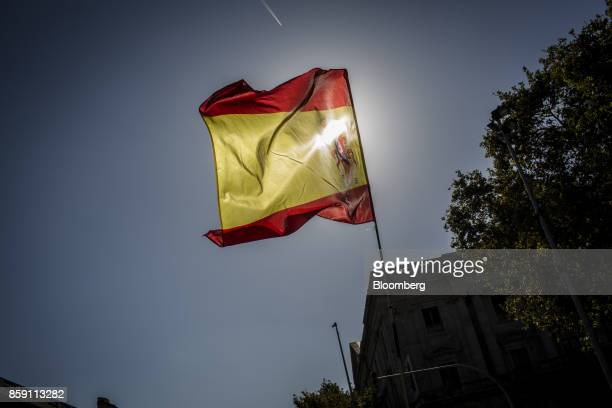 A Spanish national flag flies during a protest for Spanish unity at the Pla de Palau square in Barcelona Spain on Sunday Oct 8 2017 Catalan business...