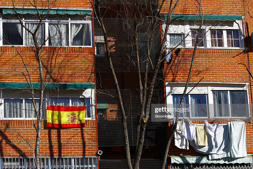 A Spanish national flag hangs from an apartment block near drying washing hanging on a line in Madrid, Spain, on Monday, Jan. 13, 2014. Spain's rental market is growing as government-spending cuts, a 26 percent jobless rate and subdued mortgage lending make home buying more difficult. Photographer: Angel Navarrete/Bloomberg via Getty Images