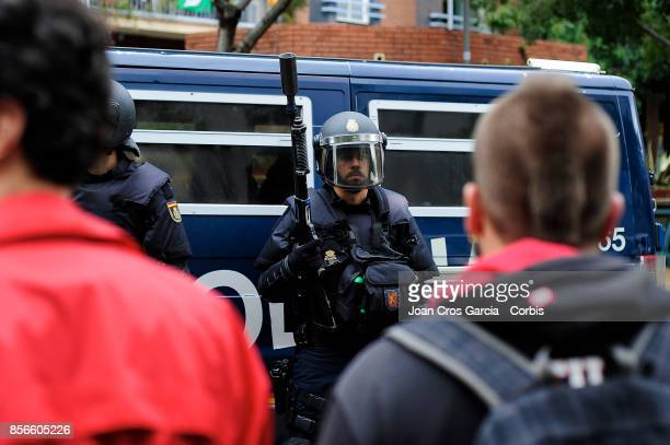 Spanish national police officer standing with a compressed air weapon during the Catalonia independence referendum declared ilegal by the Spanish...