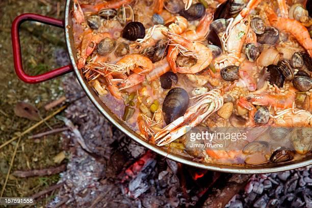 Spanische paella, die auf einem Lagerfeuer