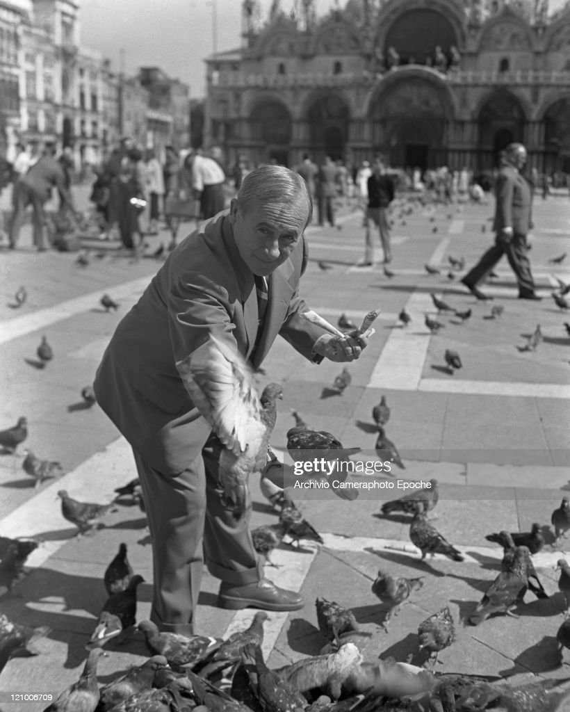Spanish painter Joan Mirò, wearing a suit and a striped tie, portrayed in St Mark's Square while feeding pigeons, Venice 1948.