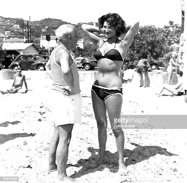 Spanish painter Pablo Picasso makes a young woman wearing a bikini smile on the beach at Golfe Juan on the Riviera Vallauris France 1960s