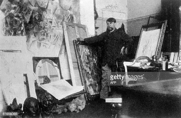 Spanish painter Pablo Picasso poses in the 20th in his Paris' Clichy studio with the largest of his canvases for the field project