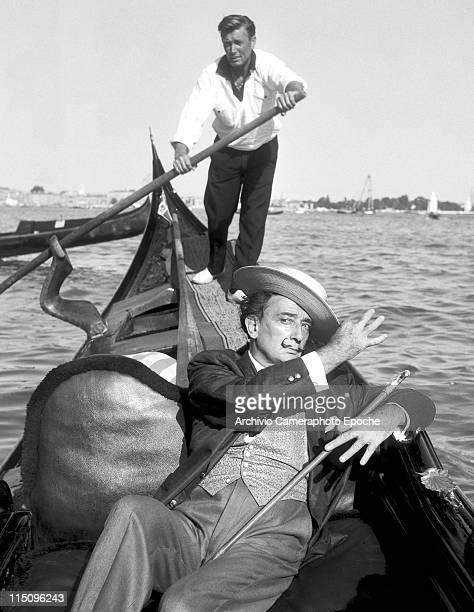 Spanish painter Salvador Dali wearing a shantung blazer and a fancy silk waistcoat a straw hat holding a walkingstick sitting on a gondola a...
