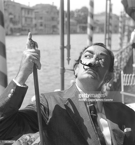 Spanish painter Salvador Dali wearing a shantung blazer and a silk tie holdind a walkingstick with a small toy gondola as a moustache sitting beside...