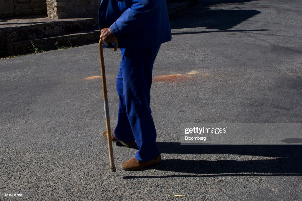 A Spanish pensioner uses a walking stick as he walks along a road in Bohoyos, Spain, on Thursday, Sept. 26, 2013. Prime Minister Mariano Rajoy is increasingly dependent on the pension reserve fund as it reaps lower returns on Spanish sovereign debt, which comprise 97.5 percent of its investments. Photographer: Antonio Heredia/Bloomberg via Getty Images