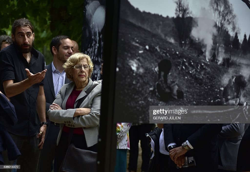 Spanish photographer Manu Brabo (L) presents his photos to Mayor of Madrid, Manuela Carmena (2L) during the opening of the exhibition 'Caminos de Exilio' ('Ways of Exile') at Retiro Park in Madrid, on 31 May 2016. The exhibition shows pictures of refugees taken by five photographers; Sima Diab (Syria), Giorgios Moutafis (Greece), Manu Brabo (Spain), Olivier Jobard (France) and Pierre Marsaut (France) and has been organized by the French Embassy and the French Institute in Spain, on the sidelines photo festival of PhotoEspana 2016. / AFP / GERARD