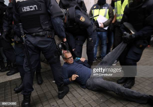 Spanish police clear the entrance of a polling station in Barcelona on October 1 on the day of a referendum on independence for Catalonia banned by...
