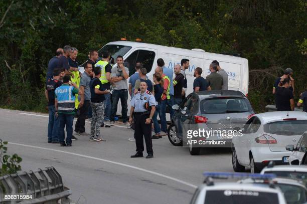 Spanish police members stand past the van of the funeral services carrying the body of Moroccan suspect Younes Abouyaaqoub on the site where he was...