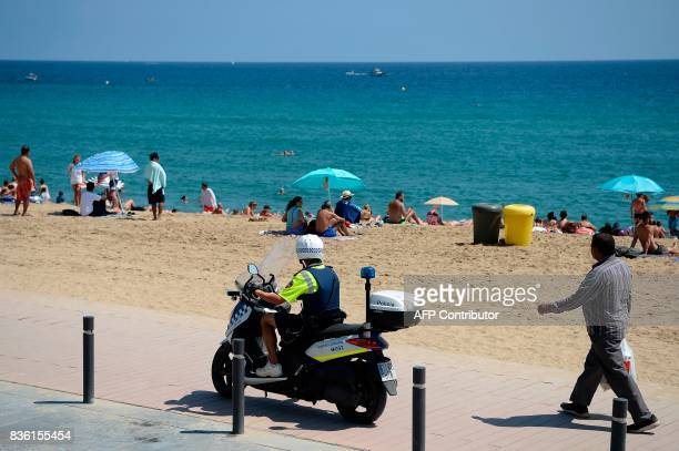 A Spanish police motorcyclist patrols on a pedestrian street next to a beach of Barcelona on August 21 2017 four days after the Barcelona and...