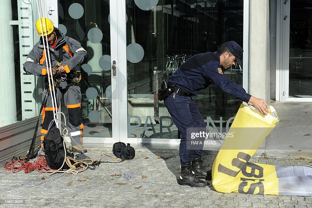 A Spanish police officer folds a banner of environmental group Greenpeace, after a protest during the third day of the trial over the sinking of the Prestige in Coruna, on November 13, 2012. Ten years after the sinking of the Prestige oil tanker off Spain, the ship's Greek captain and three others went on trial over the worst oil spill in the country's history. But environmental groups complain that key people responsible for the disaster were missing from the trial and warned that the lessons from the oil spill -- one of the worst in history -- had not been learnt.