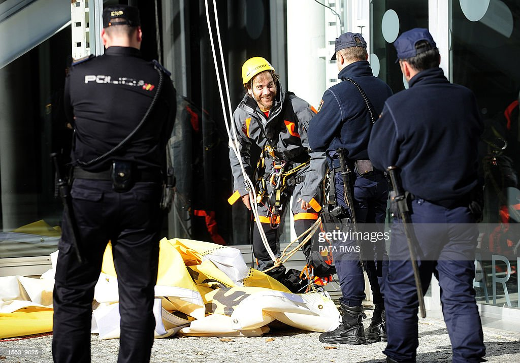 Spanish police officers check the identity of an activst of the environmental group Greenpeace, after a protest during the third day of the trial over the sinking of the Prestige in Coruna, on November 13, 2012. Ten years after the sinking of the Prestige oil tanker off Spain, the ship's Greek captain and three others went on trial over the worst oil spill in the country's history. But environmental groups complain that key people responsible for the disaster were missing from the trial and warned that the lessons from the oil spill -- one of the worst in history -- had not been learnt.