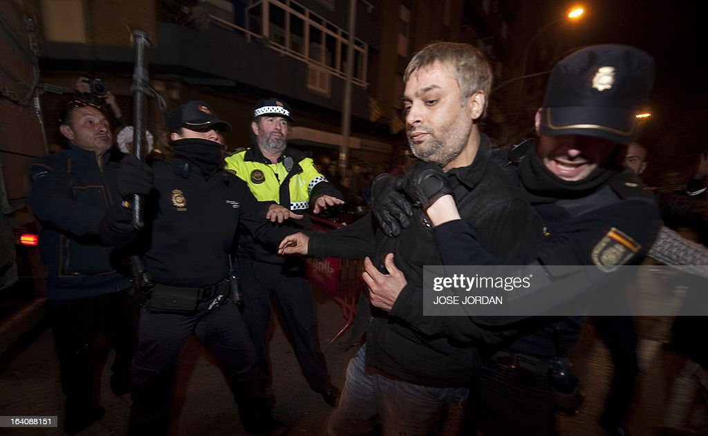 Spanish police officers detain a man after he tried to immolate himself in front of a Falla, a gigantic sculpted structure of cardboard and wood which humorously portrays relevant current events and personalities, caricaturing elephant-headed Hindu god Lord Ganesha in Valencia on March 19, 2013. The Fallas will be burned in the streets of Valencia today, as a tribute to St Joseph, patron saint of the carpenters' guild. AFP PHOTO / JOSE JORDAN