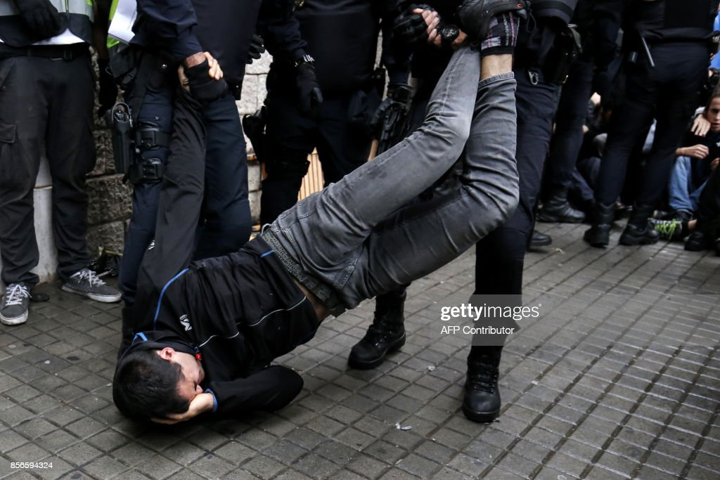 Spanish police officers drag a man as they try to disperse voters arriving to a polling station in Barcelona, on October 1, 2017 during a referendum on independence for Catalonia banned by Madrid. /