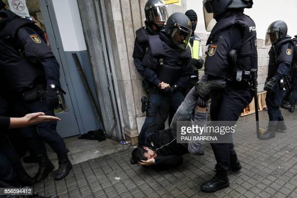 TOPSHOT Spanish police officers drag a man as they try to disperse voters arriving to a polling station in Barcelona on October 1 2017 during a...