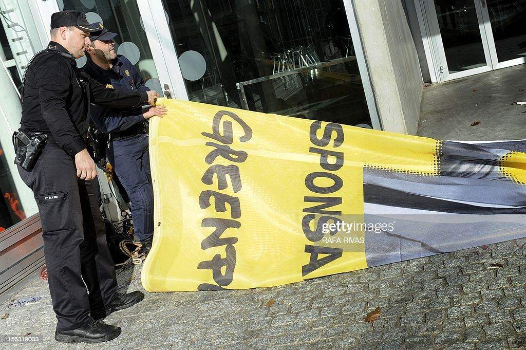 Spanish police officers fold a banner of environmental group Greenpeace, after a protest during the third day of the trial over the sinking of the Prestige in Coruna, on November 13, 2012. Ten years after the sinking of the Prestige oil tanker off Spain, the ship's Greek captain and three others went on trial over the worst oil spill in the country's history. But environmental groups complain that key people responsible for the disaster were missing from the trial and warned that the lessons from the oil spill -- one of the worst in history -- had not been learnt. AFP PHOTO / RAFA RIVAS