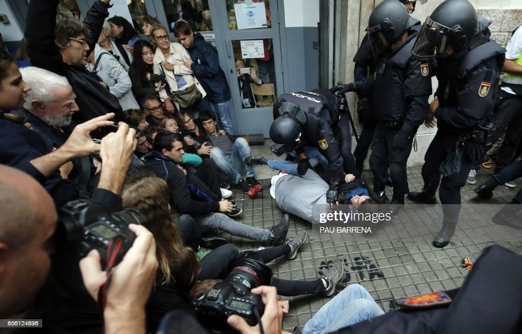 TOPSHOT - Spanish police officers immobilize some people outside a polling station in Barcelona, on October 1, 2017, on the day of a referendum on independence for Catalonia banned by Madrid. More than 5.3 million Catalans are called today to vote in a referendum on independence, surrounded by uncertainty over the intention of Spanish institutions to prevent this plebiscite banned by justice. BARRENA