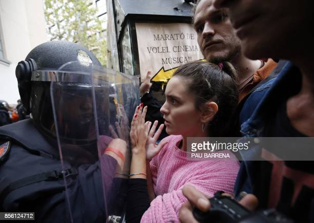 TOPSHOT Spanish police push people with a shield outside a polling station in Barcelona on October 1 on the day of a referendum on independence for...