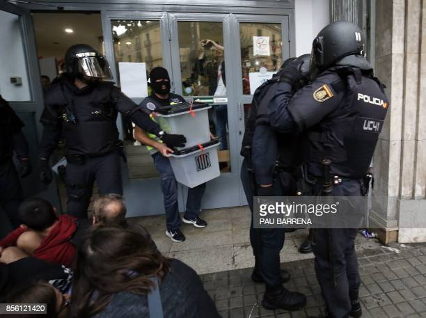 Spanish police seize ballot boxes in a polling station in Barcelona on October 1 on the day of a referendum on independence for Catalonia banned by...