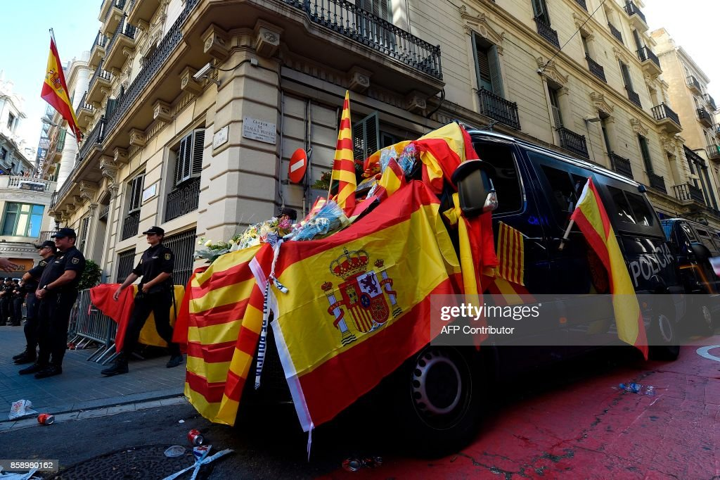 Spanish police vans are decorated with Spanish and Catalan flags by protesters during a demonstration called by 'Societat Civil Catalana' (Catalan Civil Society) to support the unity of Spain on October 8, 2017 in Barcelona. Ten of thousands of flag-waving demonstrators packed central Barcelona to rally against plans by separatist leaders to declare Catalonia independent following a banned secession referendum. Catalans calling themselves a 'silent majority' opposed to leaving Spain broke their silence after a week of mounting anxiety over the country's worst political crisis in a generation. GENE
