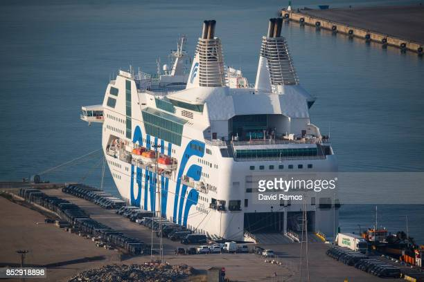 Spanish Police vans are parked next to a ferry ship rented by the Spanish Interior Ministry to house National Police and Civil Guard police officers...