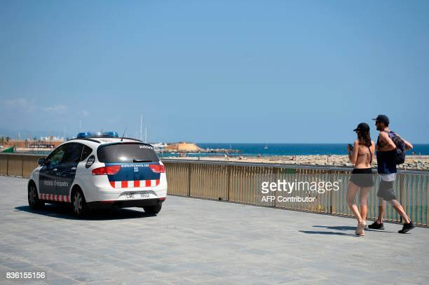 A Spanish police vehicle patrols on a pedestrian street next to a beach of Barcelona on August 21 2017 four days after the Barcelona and Cambrils...