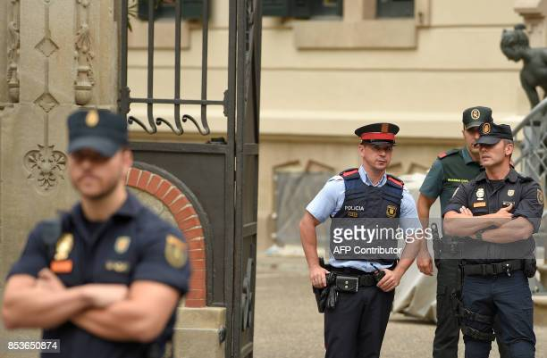 TOPSHOT A Spanish policeman a Spanish Guardia Civil guard and a Catalan policeman known as Mossos d'Esquadra stand guard during a coordination...