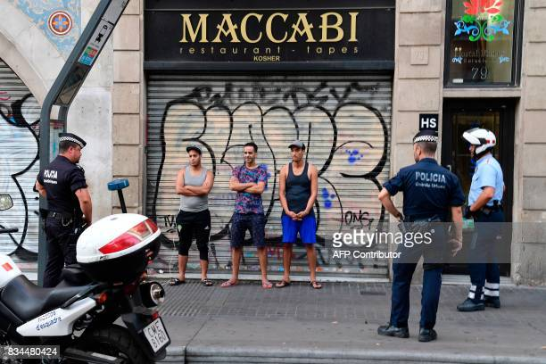 Spanish policeman control the identity of three men on the Rambla boulevard on August 18 2017 a day after a van ploughed into the crowd killing 13...